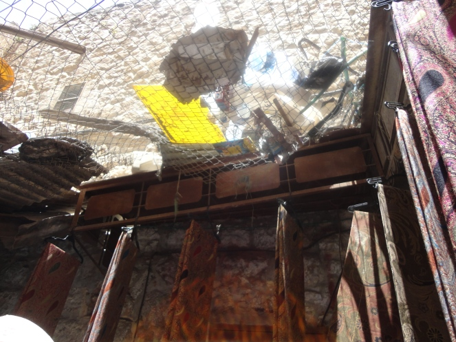 Rubbish in wire mesh covering Hebron market.